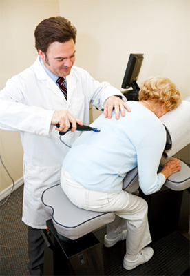 Chiropractor adjusting patient with activator instrument